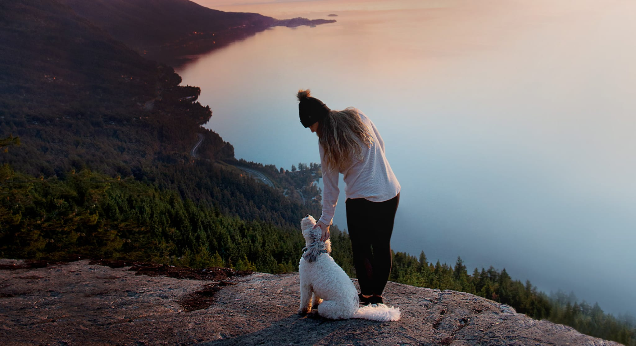 Woman petting dog on mountain overlooking lake and forest
